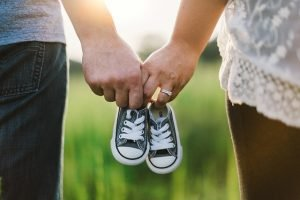 A couple holding baby shoes.