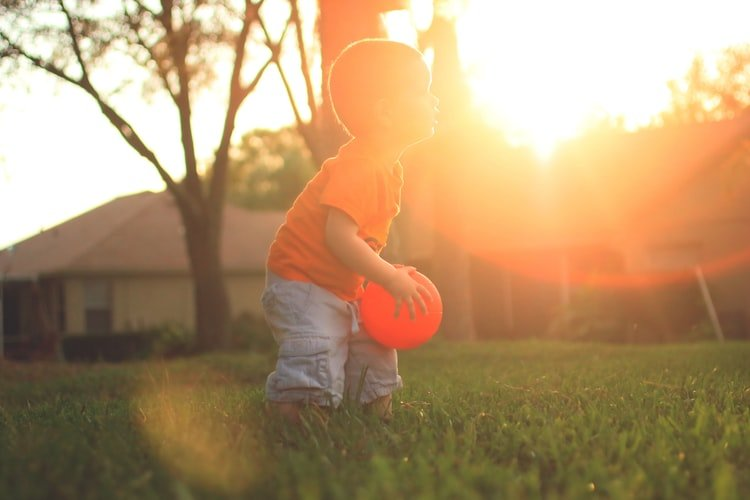 toddler playing in the sunset