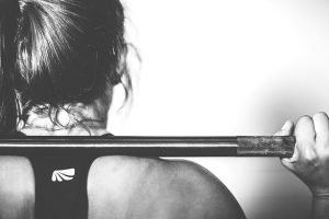 Woman lifting weights and thinking about reasons why people rent storage units