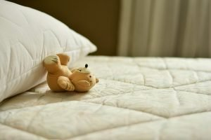 Teddy bear on a bed with no sheets