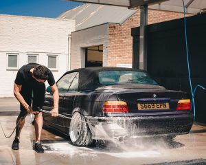 a man washing a black car