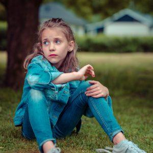 girl in denim jacket sitting on grass
