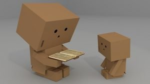 Two cardboard box robots reading a book