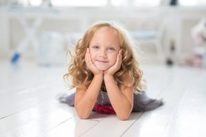 Girl smiling laying on the floor