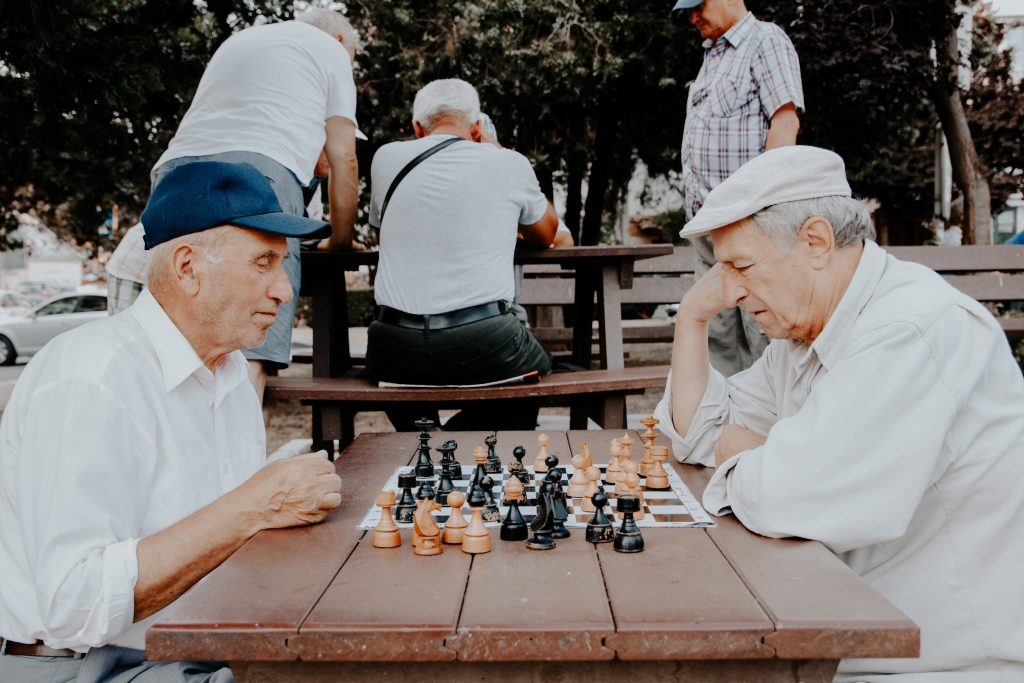 two seniors playing chess in a park