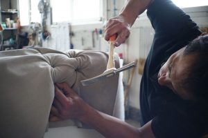 A man with his body tilted sideways while he's hammering down a nail into a piece of furniture.