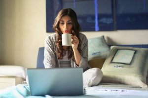 Girl drinking from a mug and reading from a laptop