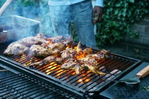 Chicken wings and legs on a charcoal grill with a man in the background cooking them.