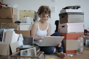 girl sitting in a cluttered room smiling, looking at a laptop
