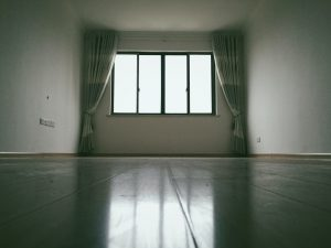 Photo of an empty apartment with nothing but polished floors and curtains; renting out an unfurnished apartment in Memphis is ideal for long-term tenants