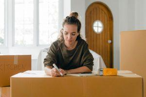 woman writing on a moving box