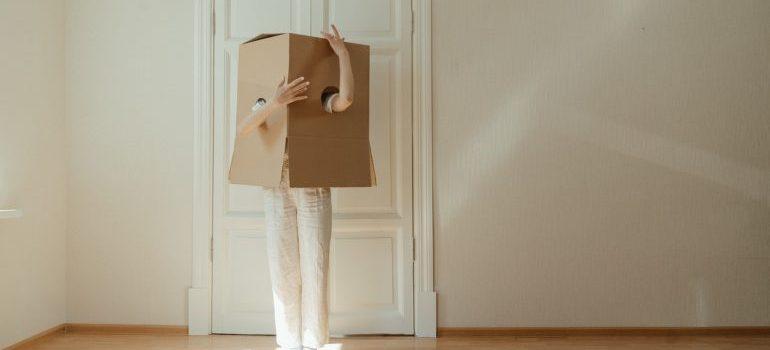 A girl playing inside a cardboard box.