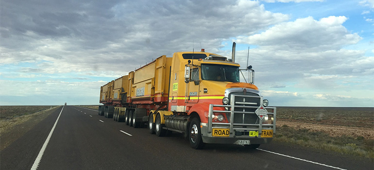A big yellow truck on a highway