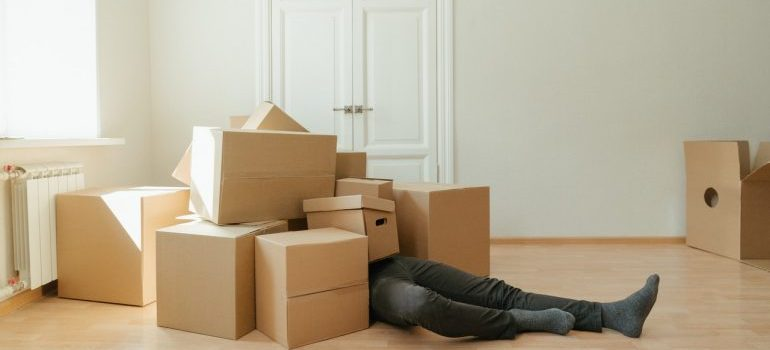 A man lying under cardboard boxes