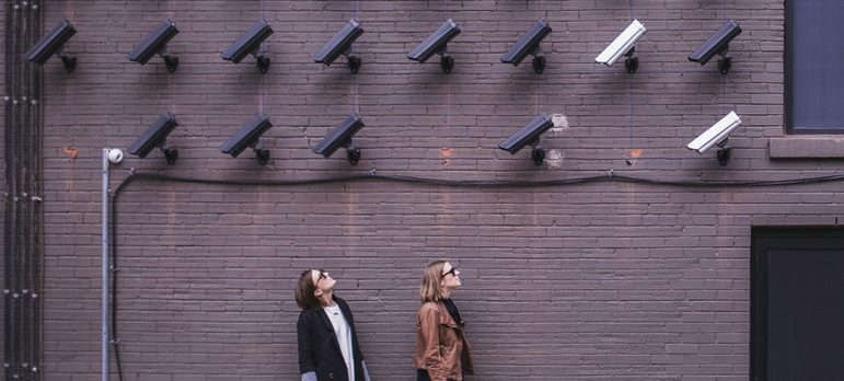 Two people standing below surveillance cameras