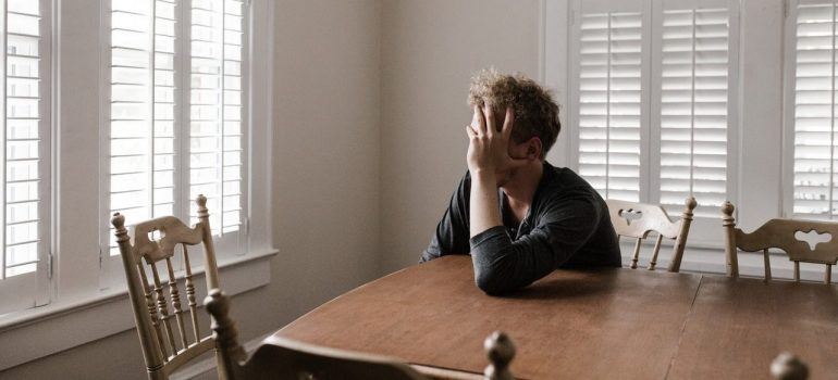 a man stressing out at the table after doing the most stressful moving tasks