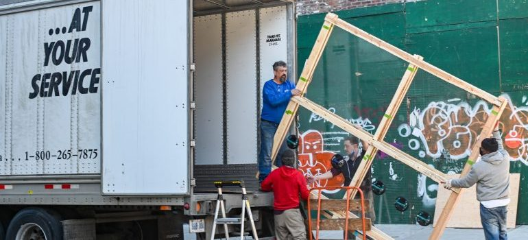 Four men are packing things into a truck