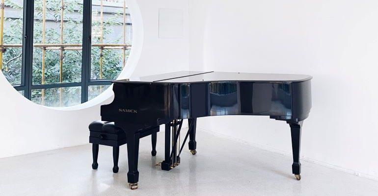 A grand piano in a white room.
