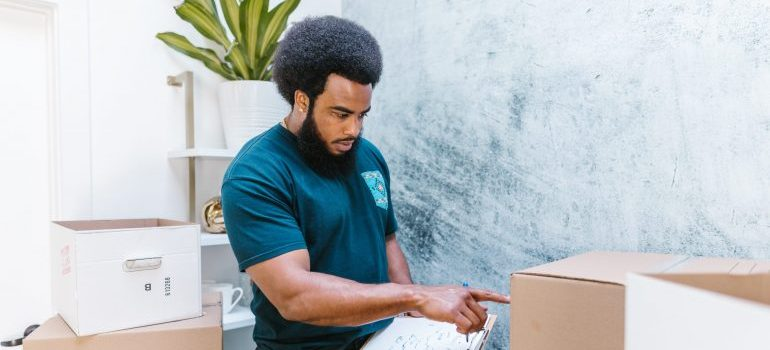 A professional mover checking moving boxes