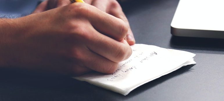 A guy writing on a paper