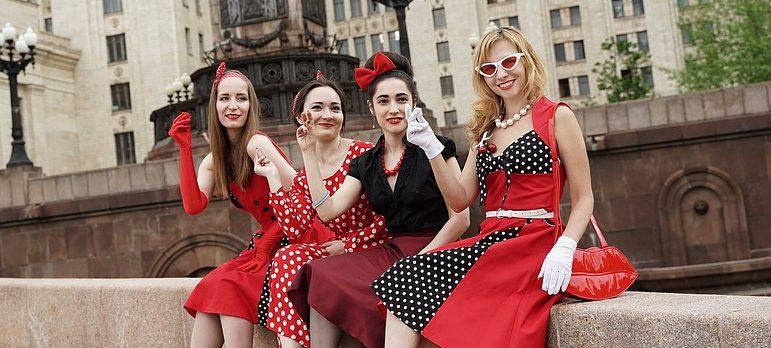 four rockabilly girls sitting on a curb
