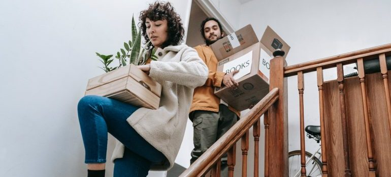 Couple carrying packed boxes down the stairs