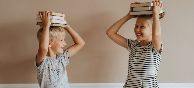 Two kids holding books on their head